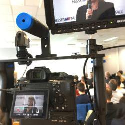 Eine Filmkamera von Sony auf einem Gestell mit einem externen Monitor filmt eine blonde Frau, die ein Mikrofon in der Hand hat. EB-Team in Aschaffenburg