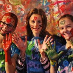 Drei Mädchen beim Action-Painting eines Ferienkurses der KULTinklusive